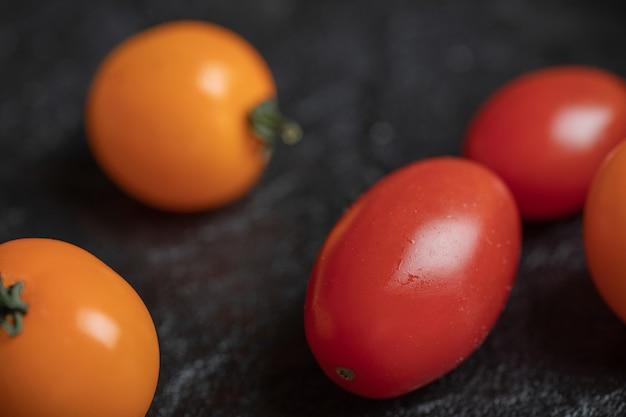 Tomates cerises jaunes et rouges sur fond noir.