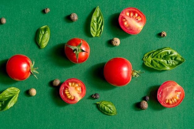 Tomates cerises juteuses coupées en deux et feuilles de basilic. concept pour une alimentation saine. vue de dessus. copiez l'espace.