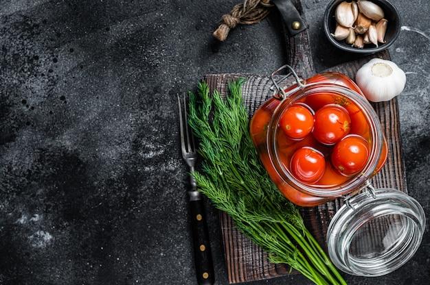 Tomates cerises marinées dans un bocal en verre avec des herbes