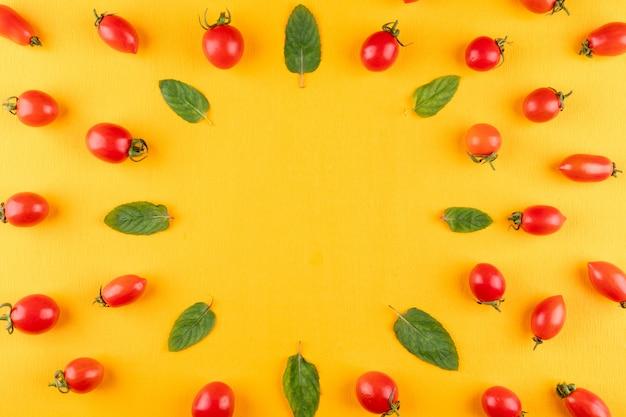 Tomates cerises et menthe vue de dessus sur une surface jaune avec copie espace