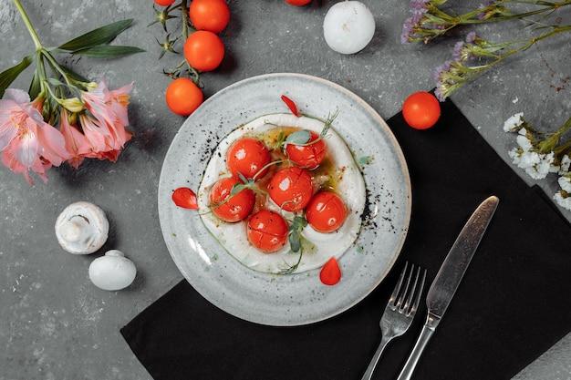 Tomates cerises avec mousse de tofu sur une assiette. lieu d'inscription.