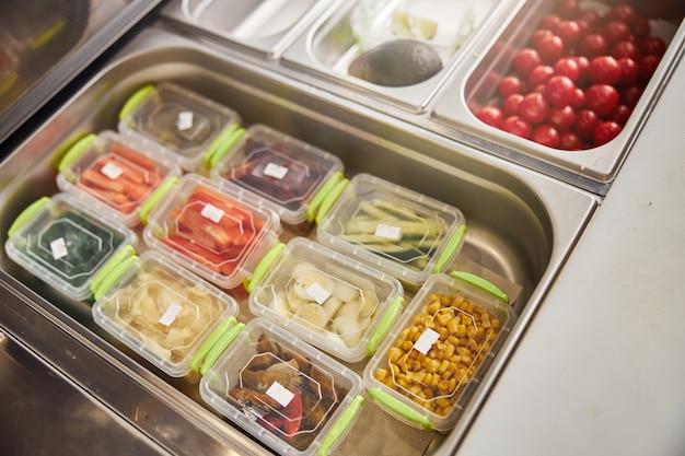 Tomates cerises mûres, avocat, concombre tranché, carotte, maïs et autres ingrédients dans des récipients en plastique avec étiquettes en pizzeria