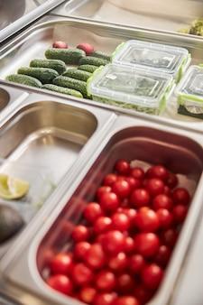 Tomates cerises mûres, avocat, concombres et ingrédients tranchés dans des récipients en plastique