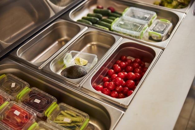 Tomates cerises mûres, avocat, concombres et légumes tranchés dans des récipients en plastique