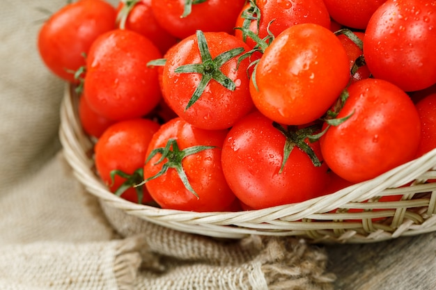 Tomates cerises mûres et juteuses avec des gouttes d'humidité dans un panier en osier. vieille table en bois, autour de la toile de jute