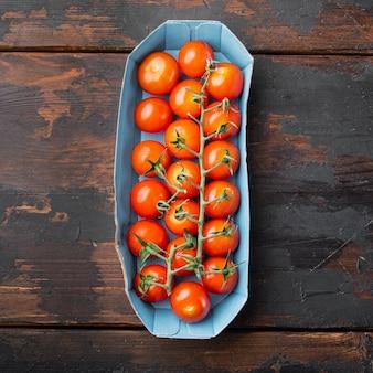 Tomates cerises mûres rouges, sur une table en bois foncé