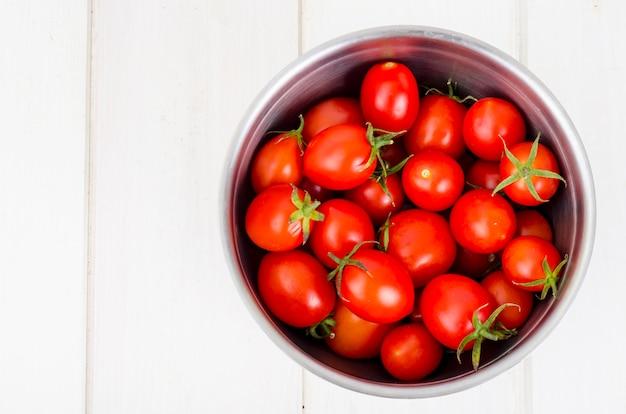 Tomates cerises mûres rouges sur table en bois.