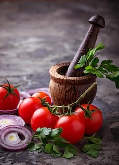 Tomates cerises, oignons rouges et mortier pour les épices. mise au point sélective