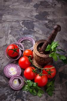 Tomates cerises, oignons rouges et mortier pour les épices