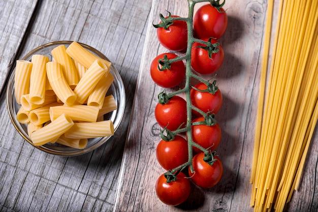 Tomates cerises et pâtes fraîches sur socle en bois.
