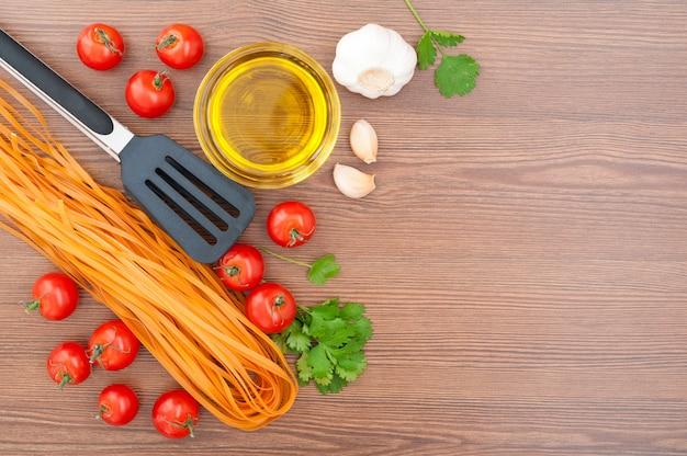Tomates cerises, pâtes, huile d'olive, ail, herbes et pinces à pâtes sur le vieux fond en bois. style rustique. cuisine italienne traditionnelle.