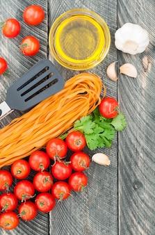 Tomates cerises, pâtes, huile d'olive, ail, herbes et pinces à pâtes sur le vieux fond en bois.