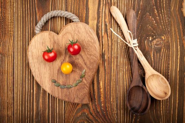 Tomates cerises sur planche à découper, cuillères en bois sur fond de bois