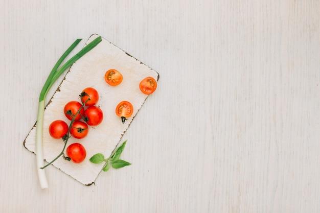 Tomates cerises; poireau et feuilles sur une planche à découper sur le bureau