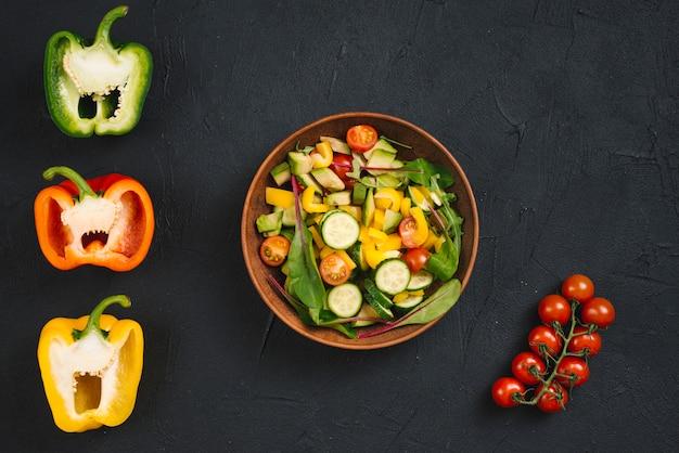 Tomates cerises; poivron coupé en deux et salade végétalienne fraîche sur fond de béton