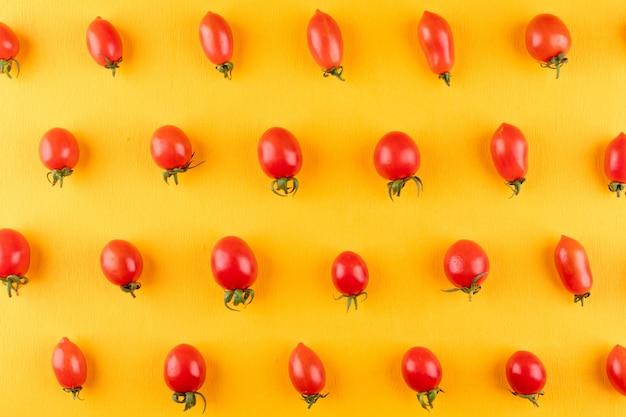 Tomates cerises rangées rangée par rangée sur jaune