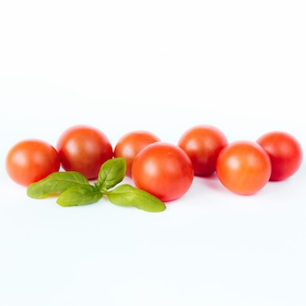 Tomates cerises rouges au basilic vert sur fond blanc