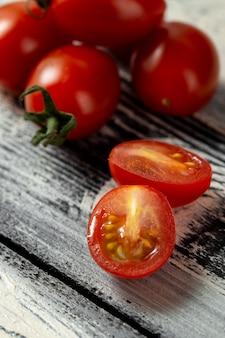 Tomates cerises rouges sur un bureau en bois gris