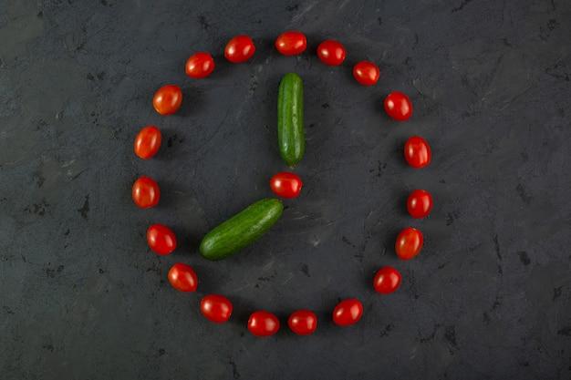 Tomates cerises rouges et concombres verts sur fond sombre