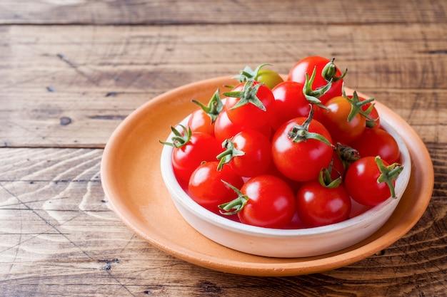 Tomates cerises rouges dans un bol en céramique sur la table en bois.