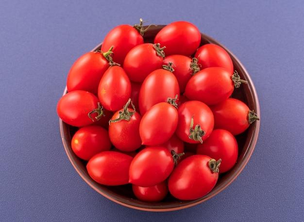 Tomates cerises rouges fraîches dans un bol en bois isolé sur fond bleu, gros plan.