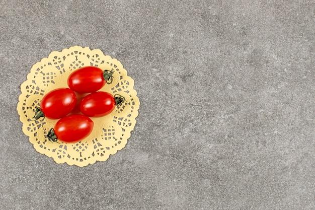 Tomates cerises rouges fraîches sur gris.