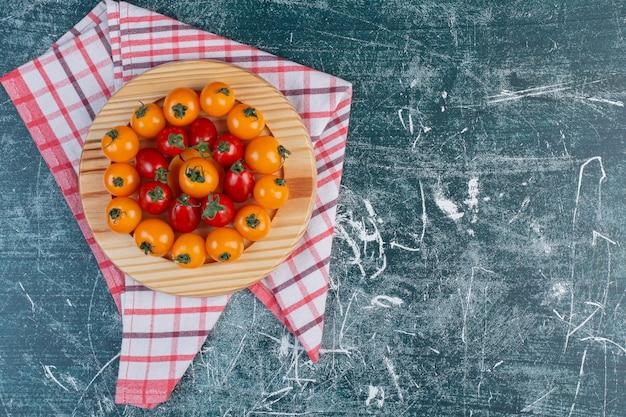 Tomates cerises rouges et jaunes sur fond bleu.