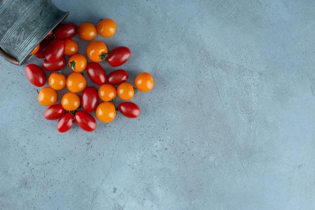 Tomates cerises rouges et jaunes sur fond gris.