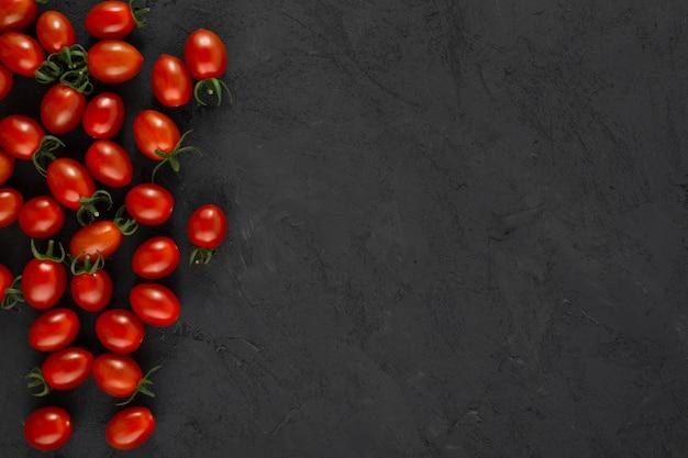 Tomates cerises rouges mûres fraîches sur fond gris