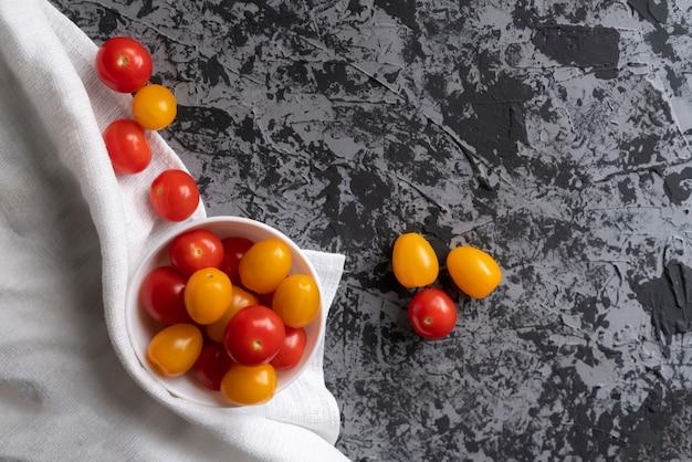 Tomates cerises et tomates jaunes sur une table de grunge, régime de tomates