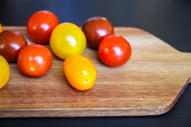 Tomates cocktail colorées sur une planche à découper en bois