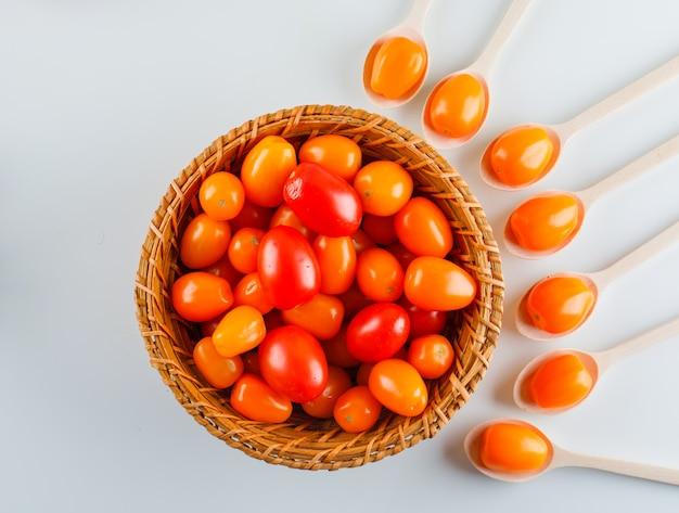 Tomates colorées dans des cuillères en bois et panier. pose à plat.