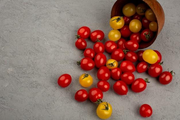 Tomates colorées rouges et jaunes fraîches mûres à l'intérieur et à l'extérieur du pot rond marron sur le bureau gris
