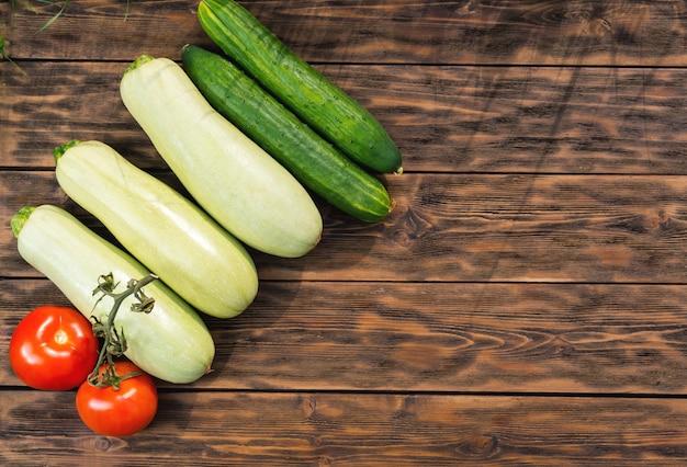 Tomates, concombres et courges sur des planches en bois