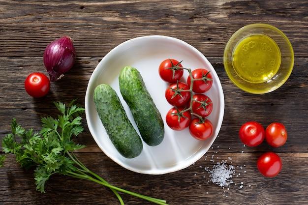 Tomates et concombres de légumes frais sur une table rustique