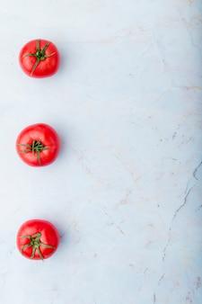 Tomates sur le côté gauche sur une surface blanche