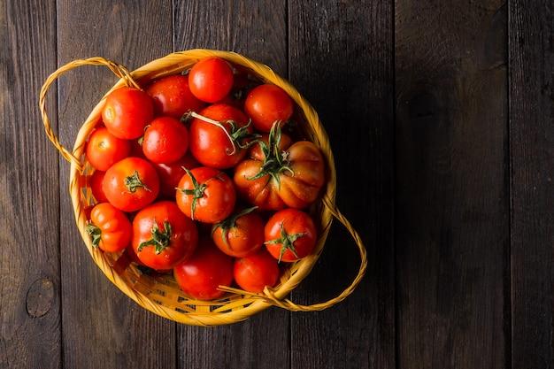 Tomates cultivées dans un potager dans un panier en osier sur une table en bois