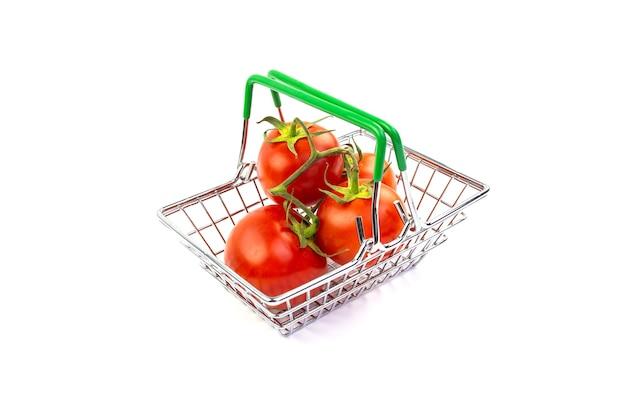 Tomates dans un petit panier en métal sur fond blanc.