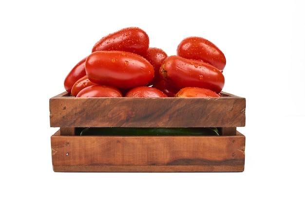 Tomates dans un plateau en bois sur le blanc.