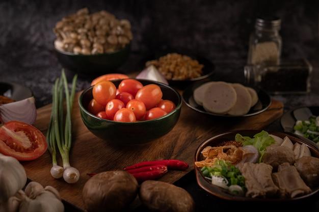 Les tomates dans la tasse noire avec des oignons nouveaux, des poivrons, des tomates et des oignons rouges.