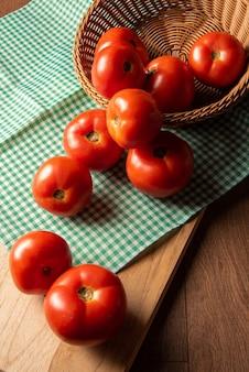 Tomates disposées dans un panier sur une nappe à carreaux et sur une table en bois