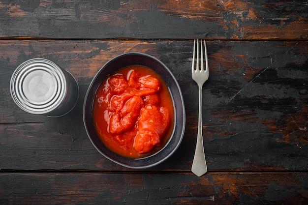 Tomates entières en conserve, sur un vieux fond de table en bois foncé, vue de dessus à plat
