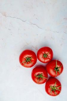Tomates entières sur surface blanche