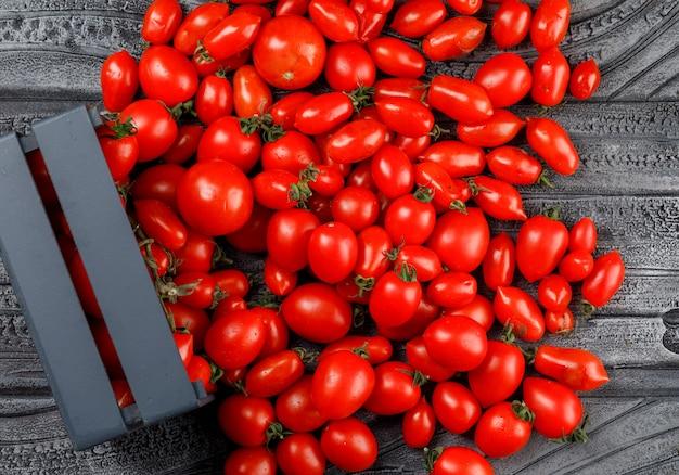 Tomates éparses d'une boîte en bois sur un mur en bois gris. vue de dessus.