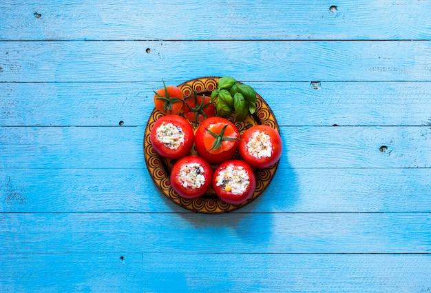 Tomates farcies au fromage et différents légumes sur un fond en bois