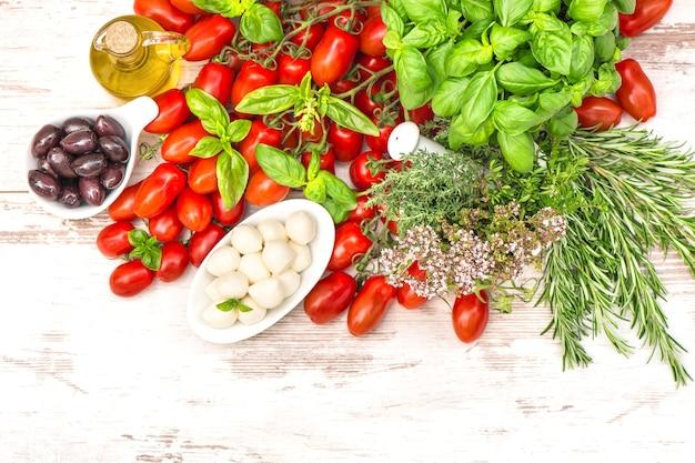 Tomates, feuilles de basilic, mozzarella et huile d'olive. fond de nourriture. ingrédients de la salade caprese