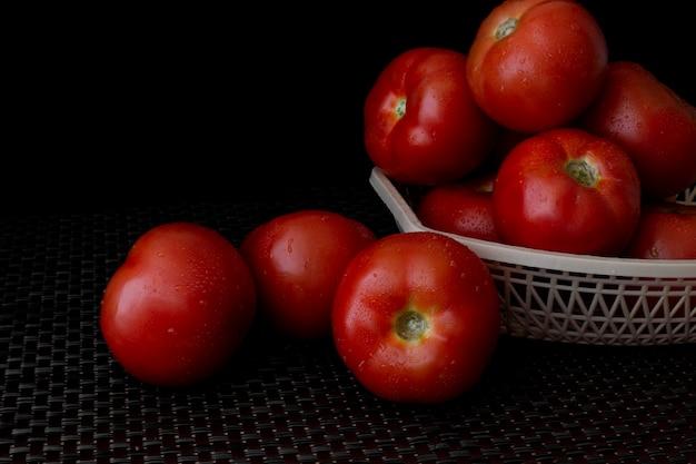 Tomates fraîches sur une assiette sur un fond sombre. un panier rempli de tomates
