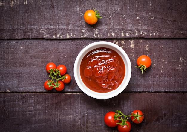 Tomates fraîches biologiques et ketchup dans une tasse de sauce tomate sur bois sombre - vue de dessus