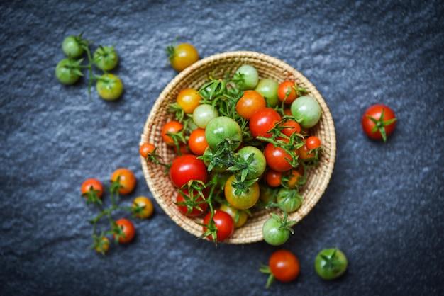 Tomates fraîches biologiques avec vert et récolte des tomates rouges mûres dans un panier sombre
