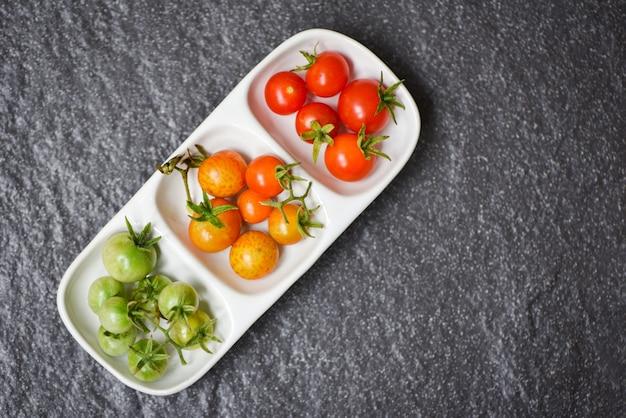Tomates fraîches cerises biologiques / tomates rouges vertes et mûres dans une tasse sombre